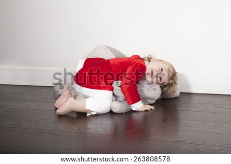 one year age caucasian blonde cute lovely tender baby barefoot Santa Claus Christmas holidays disguise lying embraced over grey plush doll on brown wooden floor white wall - stock photo