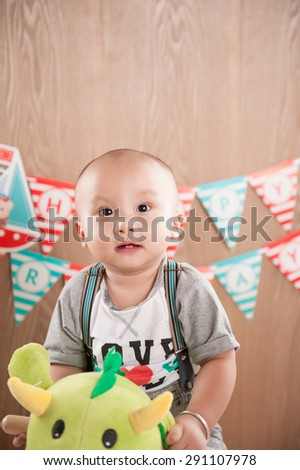 one year baby birthday party. Boy sitting on dinosaurs. Birthday banner behind.Little asian boy celebrating first birthday - stock photo