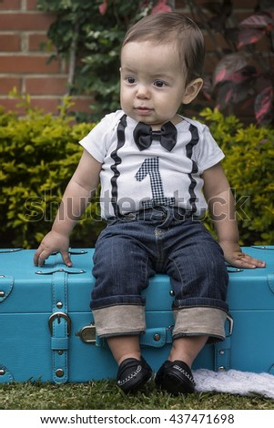One year baby boy sitting in a luggage at the garden - stock photo