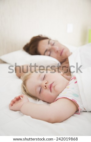 one year baby face and woman mother sleeping dreaming together in white quilt bed - stock photo