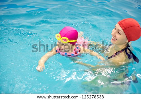 One year  baby girl at his first swimming lesson with mother - stock photo