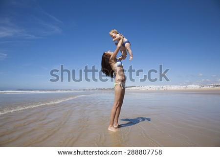 one year baby swimsuit fly in bikini woman mother arms at beach next to Conil Cadiz Spain - stock photo