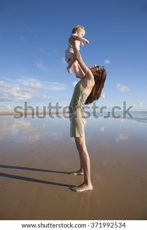 one year blonde baby fly in green dress woman mother arms at beach next to Conil Cadiz Spain - stock photo
