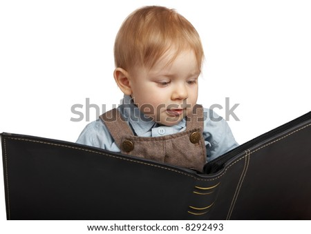 One-year boy holds an album of photos. - stock photo