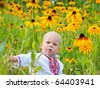 One year boy in folk shirt sitting in the field of yellow flowers. - stock photo