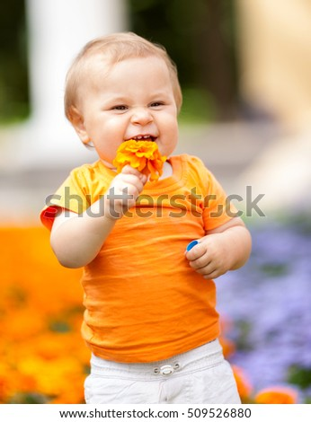 One year boy laughing with orange flower in summer park