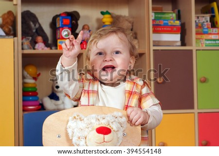 One-year boy playing and learning in preschool, he stands at the chair, gesturing; - stock photo