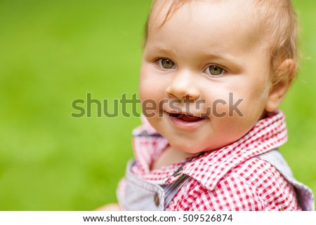 One year boy smiling portrait in summer park