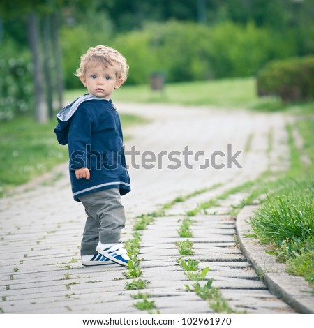 One year boy walking in the park portrait. - stock photo