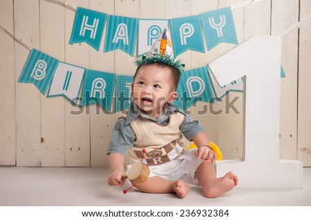 One year old Asian baby boy sitting on floor with 1 wooden letter, Happy Birthday letter on background, little pretty asian boy smiling  - stock photo