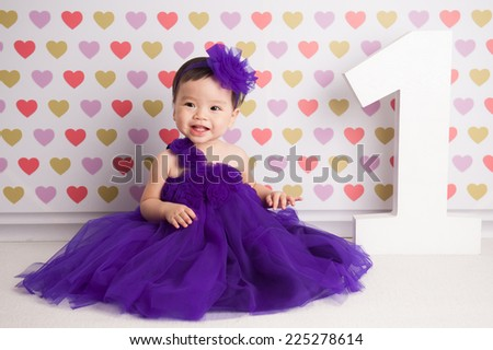 One year old Asian baby girl sitting on floor with 1 wooden letter, on pink heart background, Little pretty asian girl in violet dress smiling - stock photo
