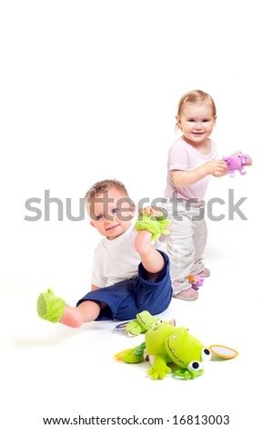 One year old babies (a boy and a girl) enjoy playing with toys. Studio Shot. All toys visible on the photo are officialy property released.