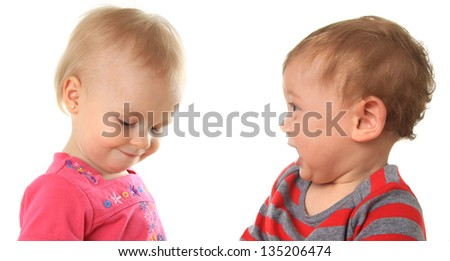 One year old babies. An eager boy and a shy girl. - stock photo
