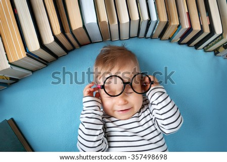 One year old baby among books with spectackle - stock photo
