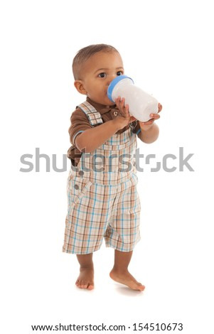 one year old baby boy holding milk bottle standing on isolated white background