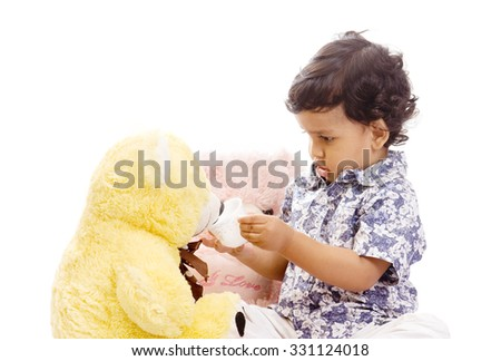 One year old baby boy playing with teddy bear toy isolated on white background Mumbai, Maharashtra, India, Southeast Asia.