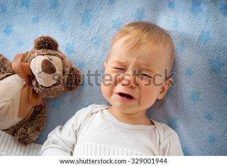 One year old baby crying in bed with a teddy bear - stock photo