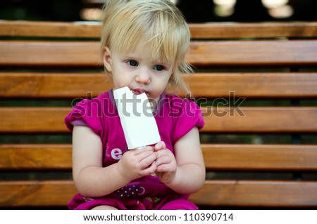 One year old baby girl eating ice cream at the park - stock photo