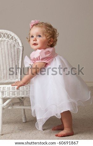 One year old baby girl in white and pink dress standing next to a white wicker chair.