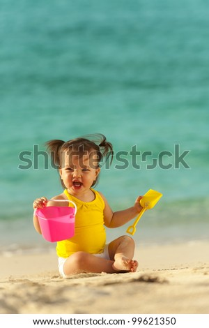 One year old baby girl playing in the sand on the beach. Ocean as background