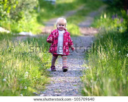 One year old baby girl walking on a road - stock photo
