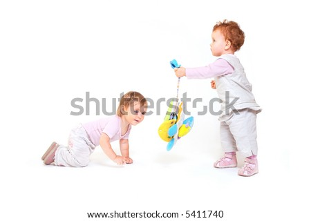 One year old baby girls  enjoy playing with toys. Studio Shot. All toys visible on the photo are officially property released.
