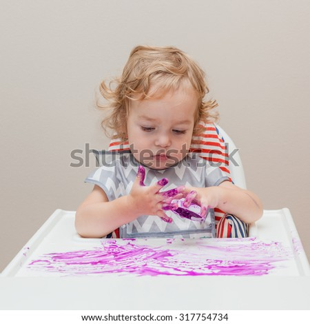 One year old baby in apron sitting on the highchair with tray, examine fingers, finger paint and his own possibility to draw and making a mess.