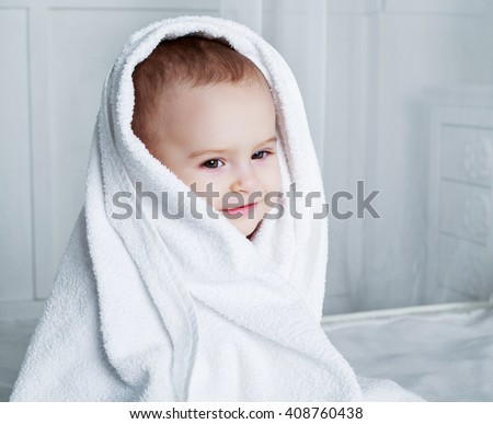 one year old baby in bed with a towel after taking a bath - stock photo