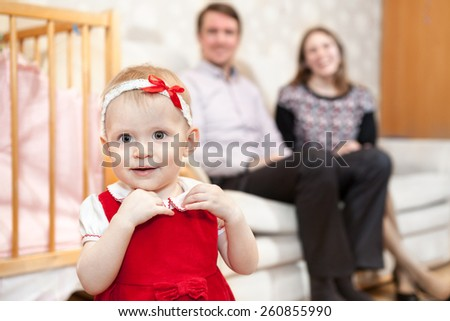 One year old baby in red dress with parents are on background - stock photo