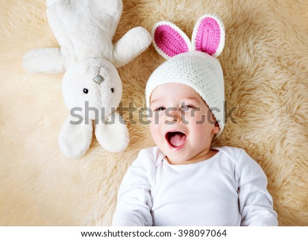 one year old baby lying in bunny hat on lamb wool - stock photo