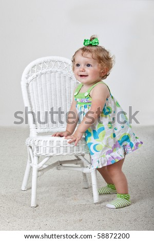 One year old baby standing next to white wicker chair. - stock photo