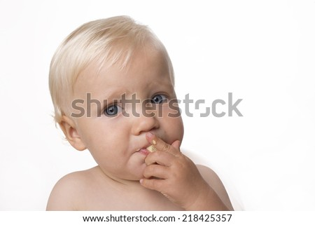 One year old boy eating himself corn snack