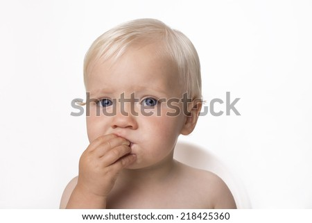 One year old boy eating himself corn snack - stock photo