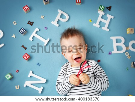 One year old child lying with spectacles and letters on blue background - stock photo