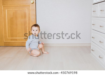 One year old cute baby boy sitting on rustic wooden floor