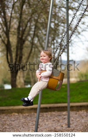 One year old girl on a swing set at a park in natural light.