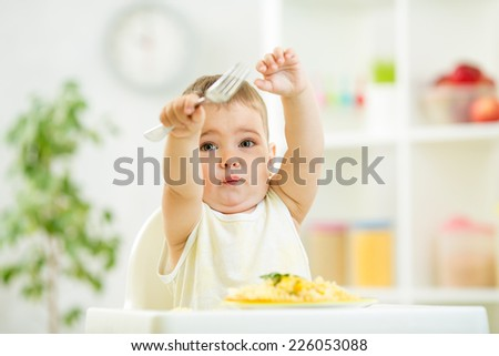 one year old kid boy in a highchair for feeding with a fork and a plate in the kitchen - stock photo