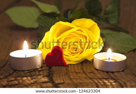 One yellow rose blossom and two tea lights with a red wooden heart on wooden board - stock photo