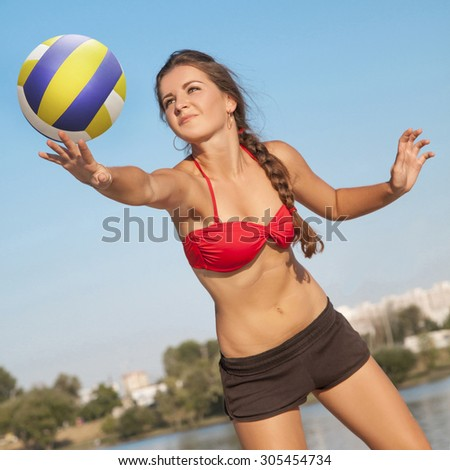 One young beautiful lady is playing volleyball on the beach  - stock photo