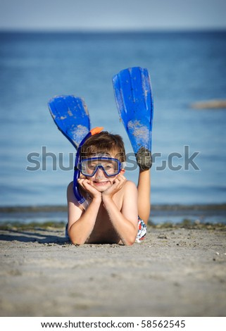 one young boy laying on a beach with snorkeling gear on