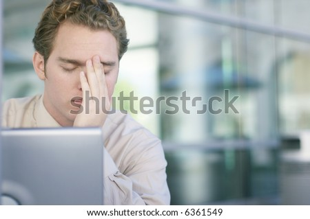 One young business man with head in hands with laptop in front - stock photo