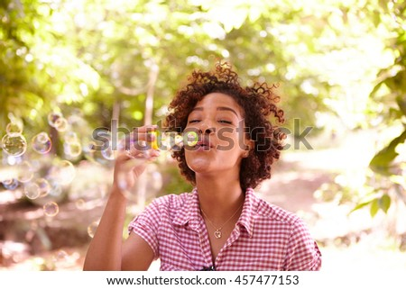 One young girl blowing bubbles with her eyes closed in the dappled afternoon sunshine with some trees around them wearing casual clothing