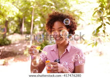 One young girl playing with bubbles with a happy smile in the dappled afternoon sunshine with some trees around them wearing casual clothing