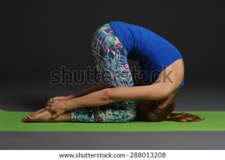 One young healthy sporty caucasian woman exercising yoga on grey studio background. - stock photo