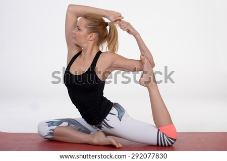 One young healthy sporty caucasian woman exercising yoga on white isolated studio background. - stock photo