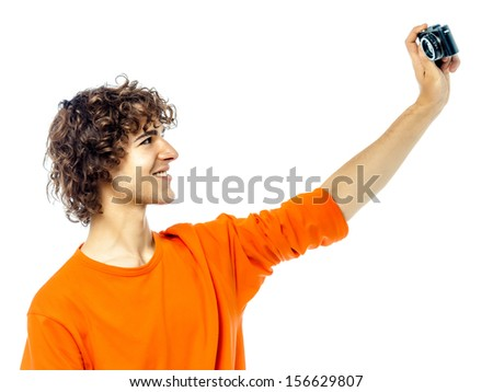one young man caucasian holding camera photographing portrait  in studio white background