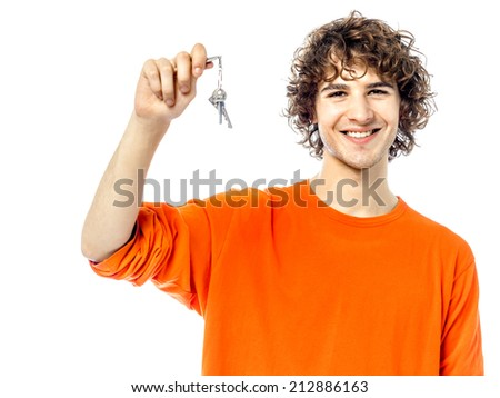 one young man  holding keys portrait in studio white background