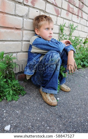 one young man sits against graffiti alone - stock photo