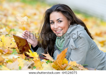 One young pretty student girl in yellow autumn leaves with computer laptop