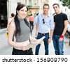One young tourist with a map and two friends in second plane - stock photo
